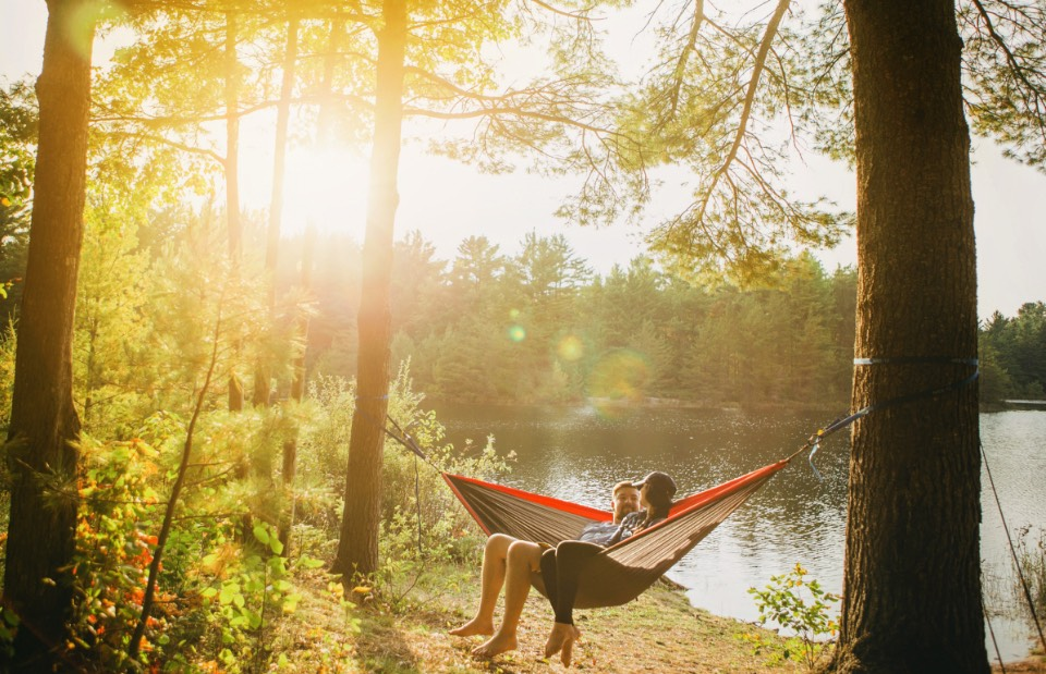 couple-sitting-in-hammock-by-lake