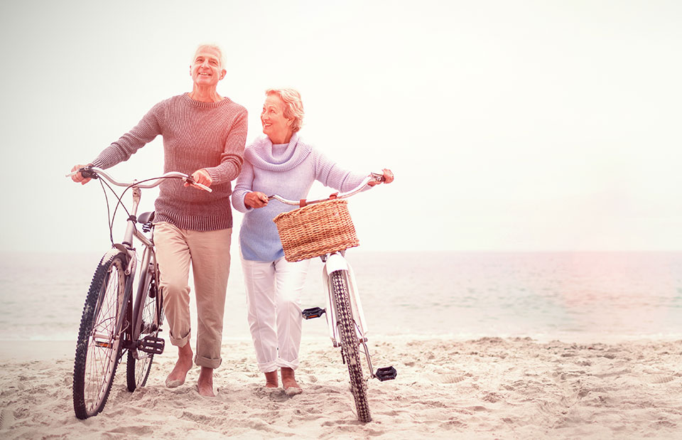 couple-walking-bicycles-on-beach