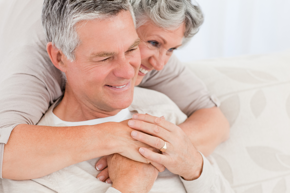 Man and woman holding each other smiling
